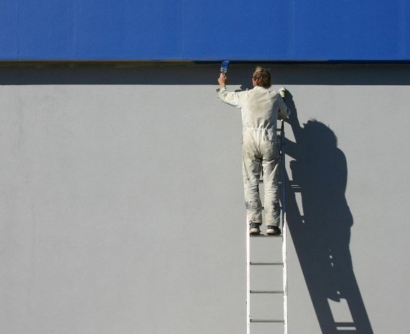 A seacoast NH Painter working on the side of a large commercial office building with blue paint on a ladder.